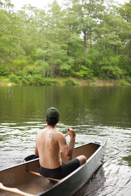 Man paddles on river in canoe