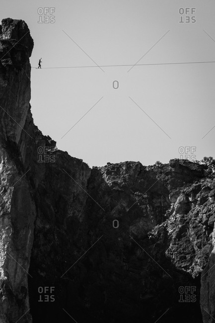 Man crossing a highline in rocky mountain cliffs in Oregon
