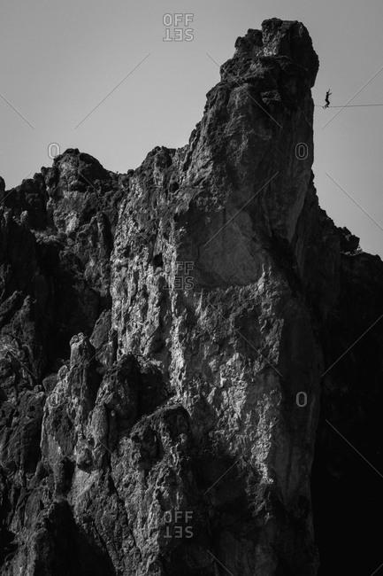 Man slacklining in rocky mountain cliffs in Oregon