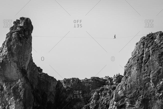 Man crossing a highline between rocky mountain cliffs in Oregon