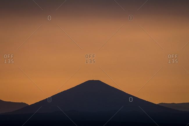 Hazy orange sky at dusk over Black Butte, Oregon