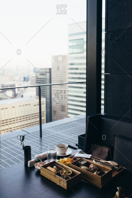 Bento and coffee on an empty table in a room high above Tokyo, Japan