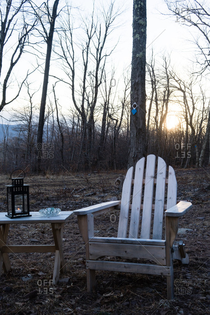 Adirondack chair and side table at a campsite in a forest