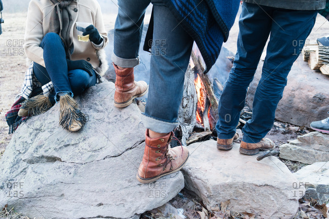 Close-up of a group of people standing around a campfire