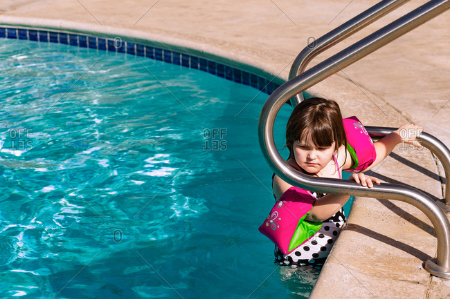 Young girl in water wings climbs into pool