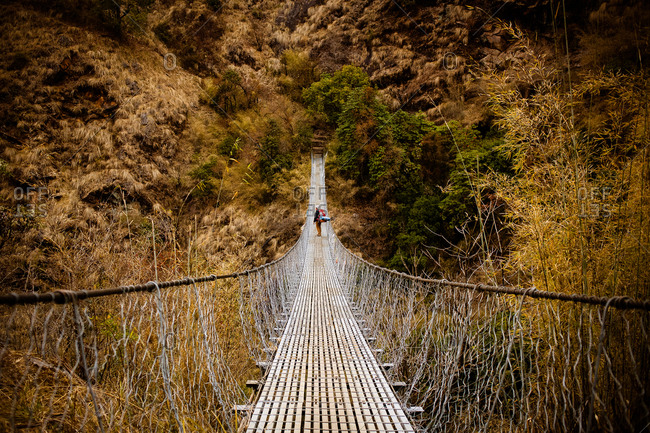 Person trekking across a narrow suspension bridge in Nepal