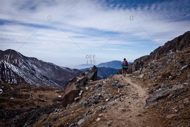 Man trekking along a rocky path, Gosikunda, Nepal