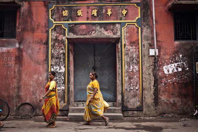 Rajasthan, India - June 2, 2014: Women walk past factory, Chinatown, Kolkata, India