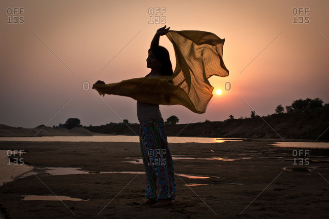 Silhouette of a woman standing along the water in West Bengal, India