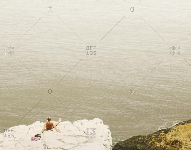 Man sunbathing on rock above the sea