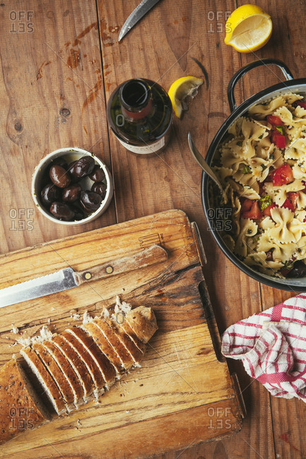 Overhead view of bread, pasta and olives served with a beer