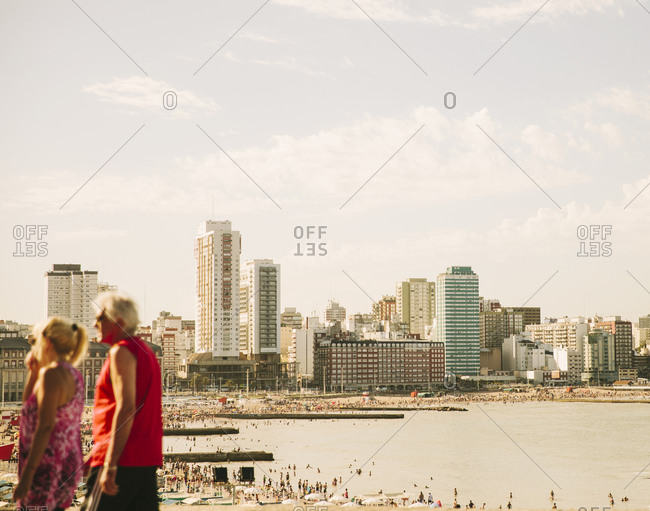 Crowded beach in front of a city skyline