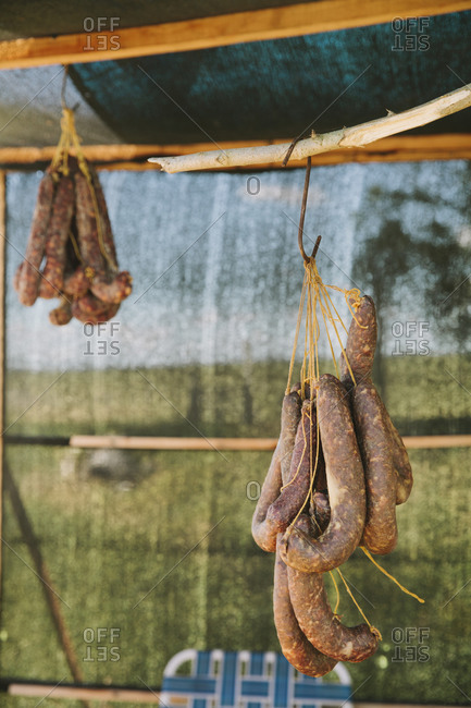 Sausages hang from rack at an outdoor market