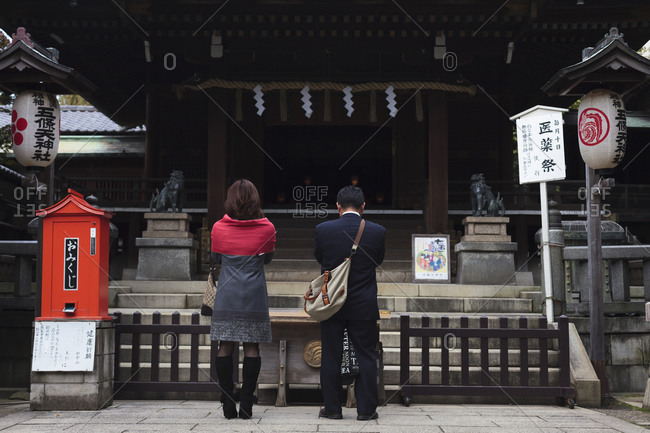 A couple praying by shinto temple