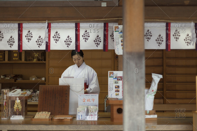 Tokyo, Japan - November 15, 2011: A woman selling products in a temple