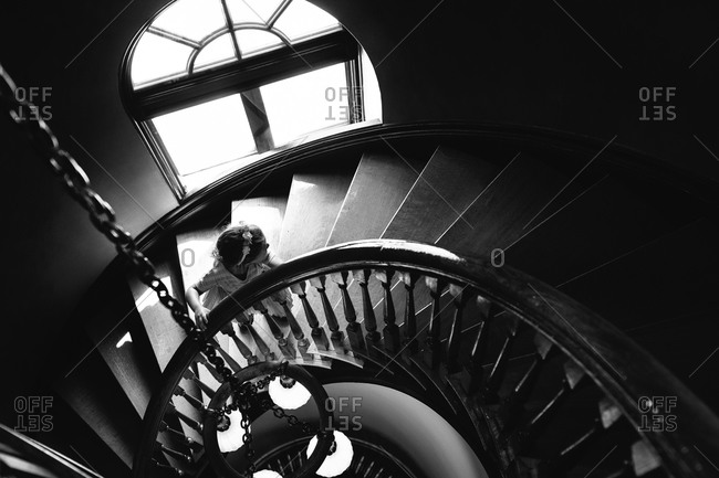 Girl walking up a sweeping staircase