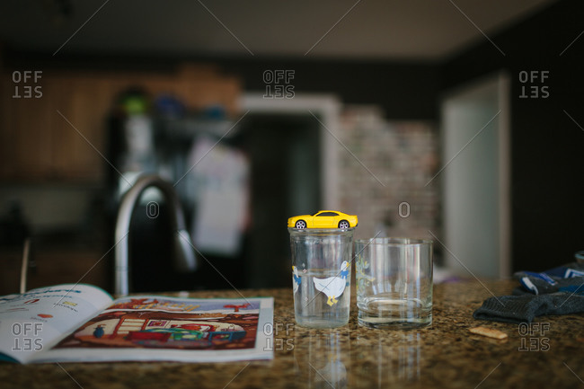Glasses, toys, and a child's workbook sitting on a kitchen countertop