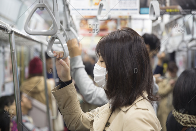 Tokyo, Japan - November 20, 2015: Woman wearing a surgical mask on the Tokyo metro in Tokyo, Japan