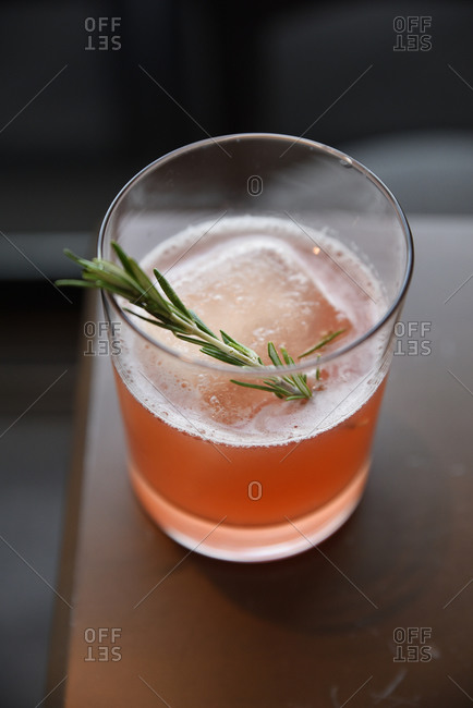 Fruity cocktail with rosemary and a large ice cube