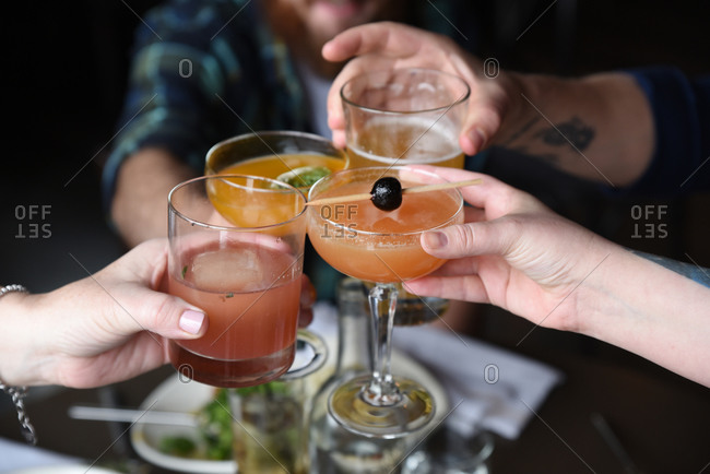 Friends making a toast with a variety of cocktails and beer
