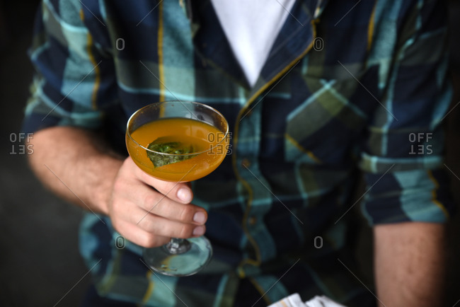 Man holding an orange cocktail in a martini glass