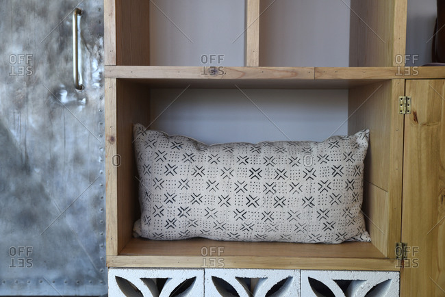 Throw pillow on a wooden shelf