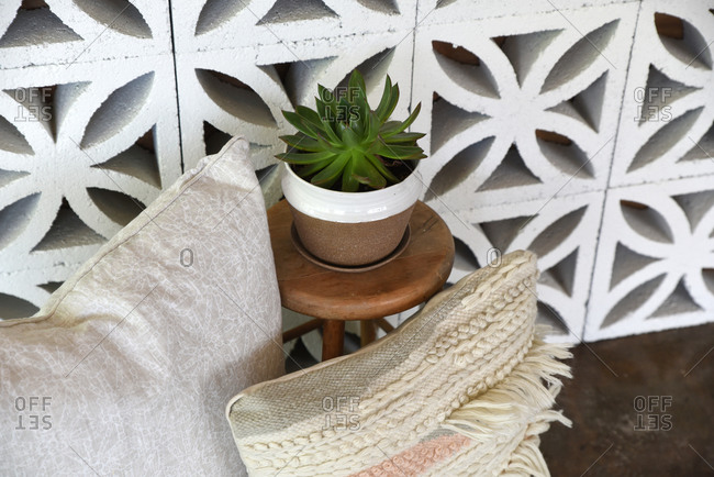 Throw pillows and a succulent against decorative cement blocks