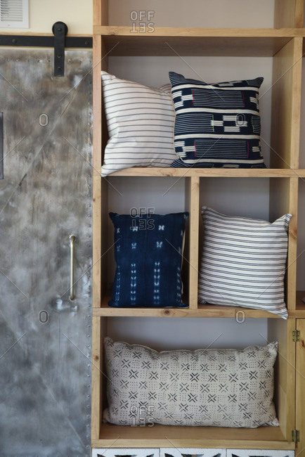 Throw pillows displayed on a wood shelving unit