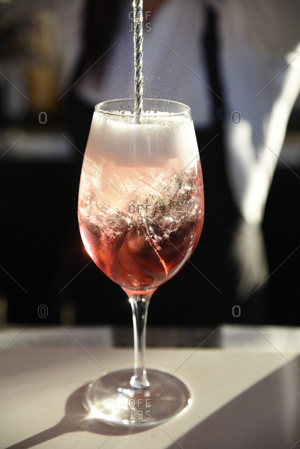 Champagne flowing into a cocktail on a bar