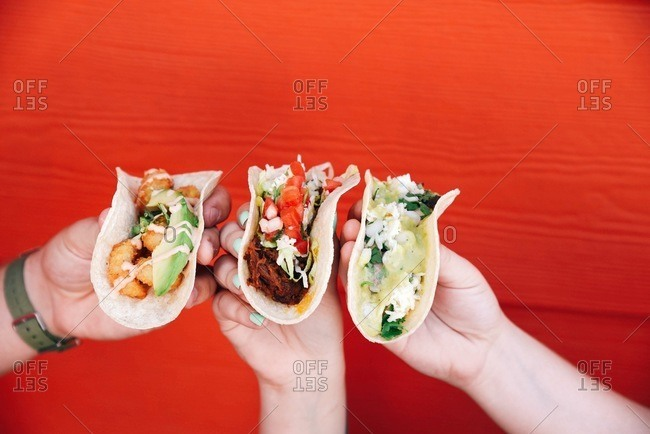 Three hands each holding a taco