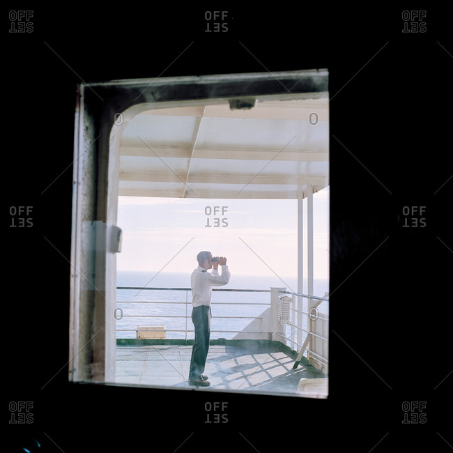 Sailor using binoculars on container ship at sea