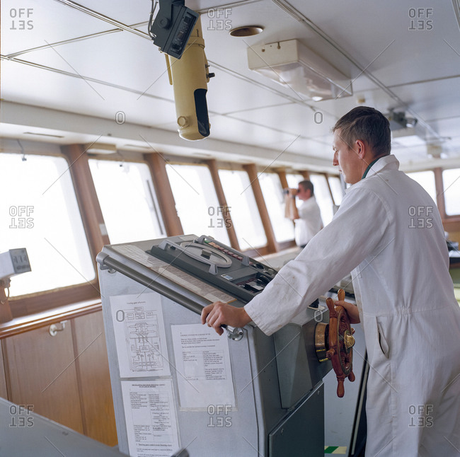 Sailor on bridge steering container ship at sea
