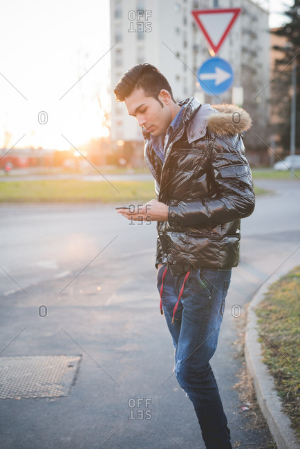 Young man using smartphone in the street, Milan, Italy