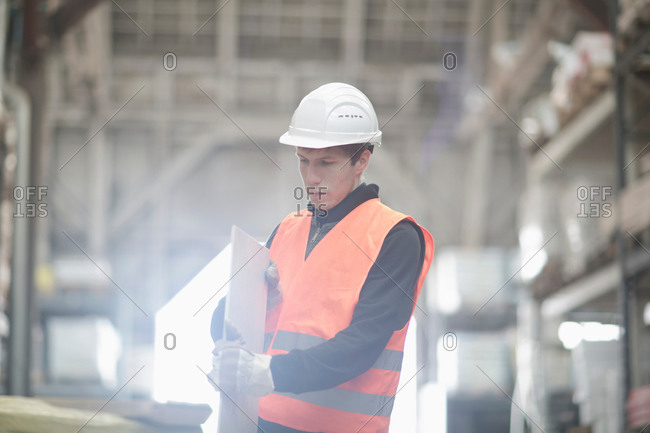 Young male warehouse worker examining plank in warehouse