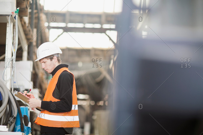 Young male warehouse worker stock taking in warehouse