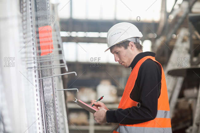 Young male warehouse worker stock taking with clipboard in warehouse