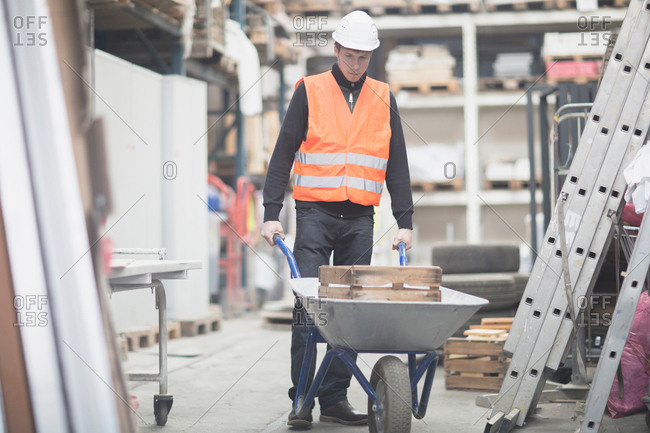 Young male warehouse worker pushing wheelbarrow in warehouse