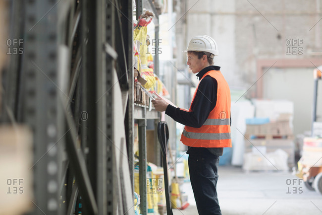 Young male warehouse worker searching shelves with clipboard in warehouse