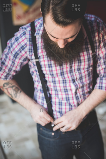 Young bearded man fastening braces onto jeans