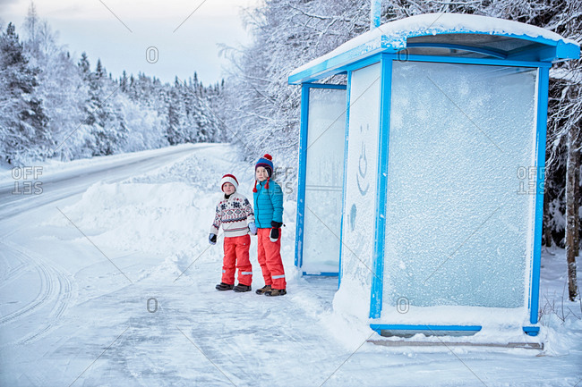 Two brothers waiting at snow covered bus stop, Hemavan, Sweden
