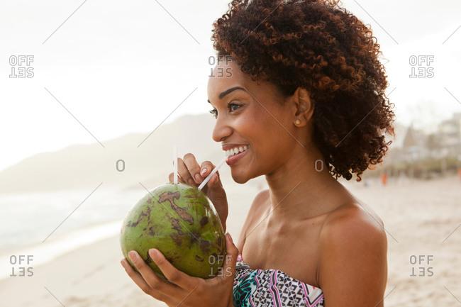 Portrait of young woman drinking coconut milk on beach, Rio De Janeiro, Brazil
