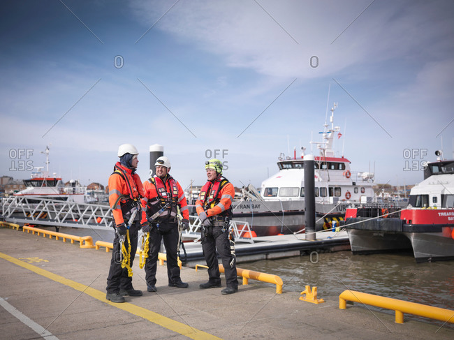 Three offshore windfarm engineers on quayside with boats in the background