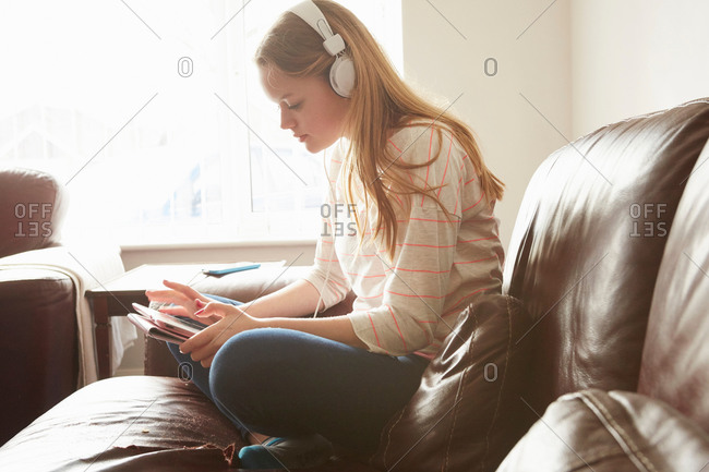 Girl on sofa wearing headphones selecting music on digital tablet
