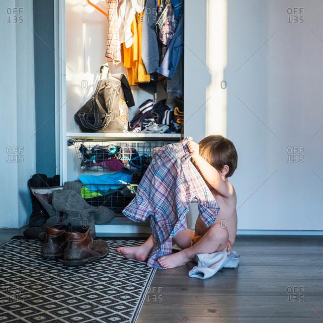 Young boy sitting next to wardrobe, holding shirt