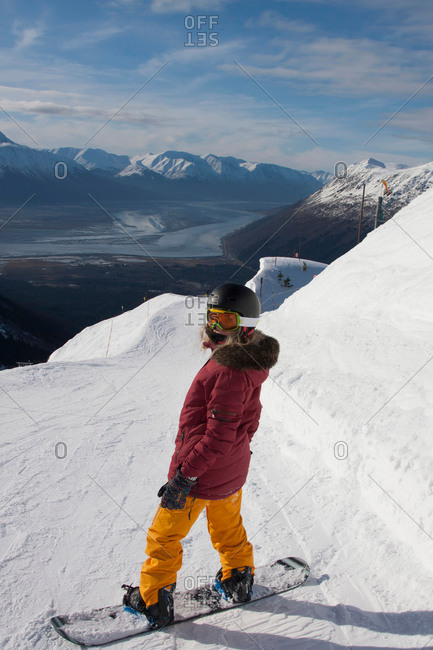 Young woman snowboarding in Girdwood, Anchorage, Alaska
