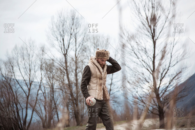 Mid adult man wearing trapper hat by trees