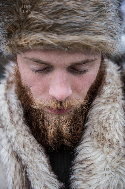 Close up of a mid adult man with a beard wearing trapper hat
