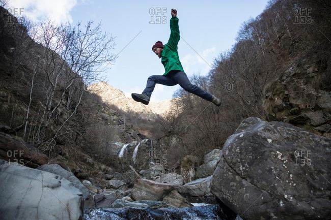 Man jumping over Toce River, Premosello, Verbania, Piedmont, Italy