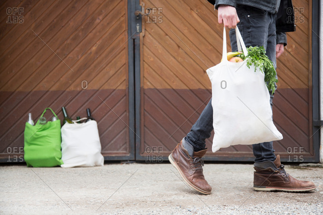 Teenage boy carrying reusable shopping bag full of fruit and veg with