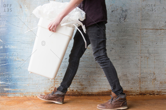 Teenage boy carrying bin with recyclable paper waste